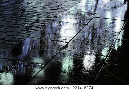 Reflection of festive illumination in puddles on pavement, Moscow, Russia