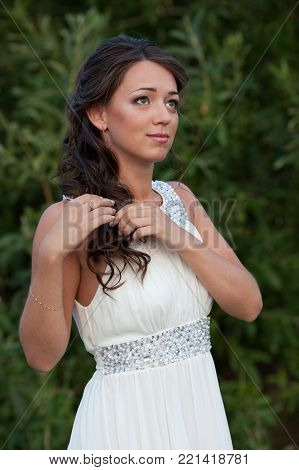 Young beautiful woman with hairstyle in white wedding dress on nature looking up