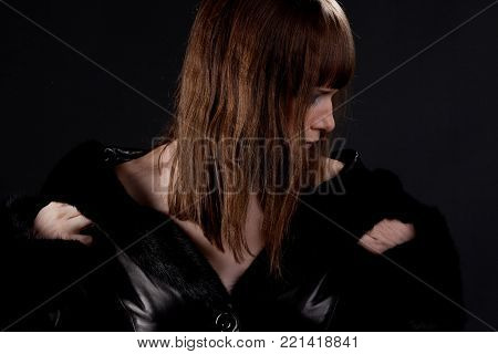 Woman in black coat looking to one side on the black background