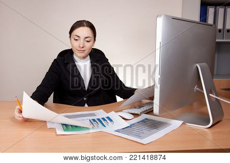 Beautiful businesswoman with financial report at office
