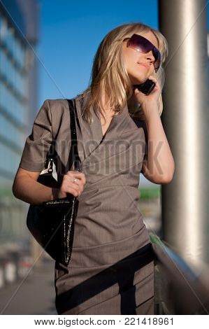 Beautiful blond woman in sunglasses and dress with cellphone walking