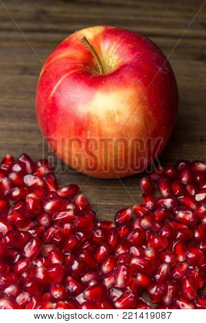 Ripe apple and pomegranate seeds opened ready for use. Apple and pomegranate fruit on a wooden surface.