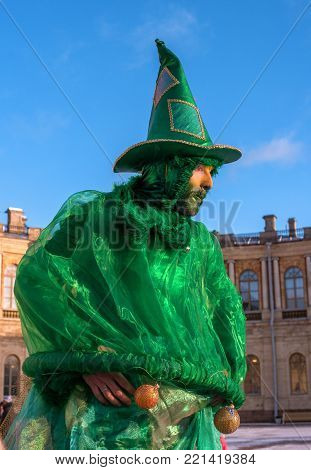 Gatchina, Russia - January 7, 2018: Christmas show for children on the parade ground in front of the Gatchina Palace. Actress on stilts as a Christmas tree.