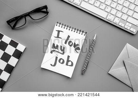 Find dream job. Handwritten motto I love my job in notebook on office desk on grey background top view.