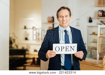 Reliable owner. Pleasant smiling occupied man standing in the bright room holding and showing the signboard.