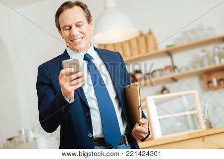 Good news. Senior occupied satisfied man standing in the room using the cellphone and holding the folder under left hand.