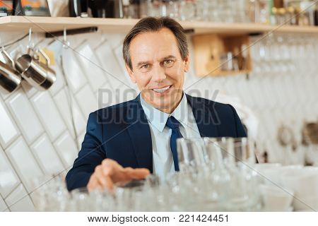 Everything must be clear. Confident occupied responsible owner standing in the shop looking straight and checking purity.