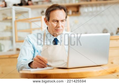 Im busy. Serious occupied pleasant man sitting in the bright room by the table using the laptop and making notices.