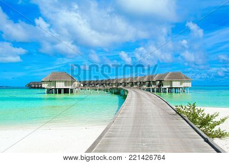 South Ari Atoll, Maldives - 12 July 2017: Beautiful tropical landscape with wooden villas of luxury resort above the crystal turquoise water of the Indian Ocean, Maldives island, 12 July 2017