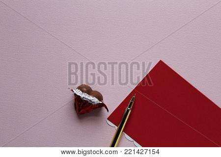 Red stationary with chocolate heart. Pink copy space.