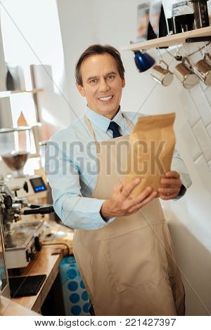 Its for you. Pleasant smiling nice-looking man in a pinafore standing in the kitchen looking straight and giving the pack.