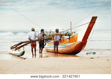 Weligama, Sri Lanka - December 21, 2017: Fishermen pushing the fishing boat out the water in the morning time in Weligama, Sri Lanka