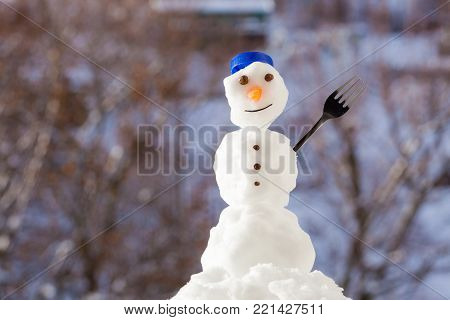 Little happy christmas snowman with blue screw top as hat and fork outdoor. Winter season and seasonal specific. Blurred background.