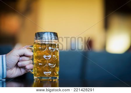 Men Hand with glass mug of golden Freshly filled beer. Real scene in bar, pub. Beer culture, Craft brewery, uniqueness beer grades, meeting of low alcohol beverage lovers. Copy space