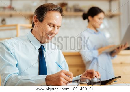 Important records. Joyful occupied senior man sitting in the room by the table smiling and writing in the notebook.