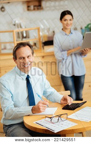Pleasant colleagues. Smiling occupied joyful man sitting in the cafe by the table looking straight and calculating.