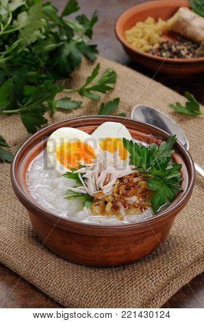 Rice porridge ginger congee with egg, chicken, crispy shallots and parsley
