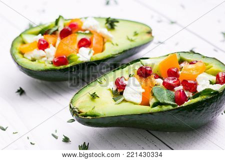 salad with avocado, fresh vegetables, feta cheese, , garnets and tangerines. healthy diet or vegetarian food on a white background.