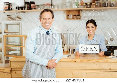 Come and smile. Friendly senior responsible man in a pinafore standing in the shop near his partner leaning to the bar and smiling.