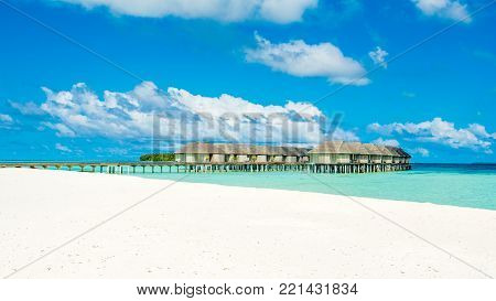 South Ari Atoll, Maldives - 12 July 2017: Beautiful tropical panoramic landscape with wooden villas of luxury resort above the crystal turquoise water of the Indian Ocean, Maldives island, 12 July 2017