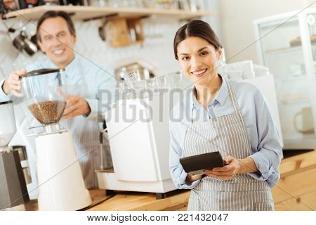 Calculate costs. Pleasant cute young woman in a pinafore standing near the kitchen smiling and using the calculator.