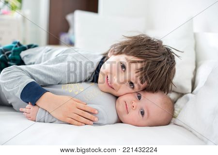 Two Children, Baby And His Older Brother In Bed In The Morning, Playing Together