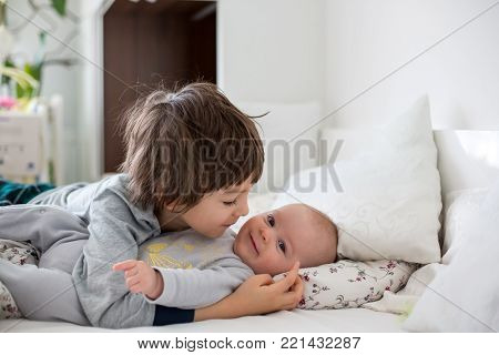 Two children, baby and his older brother in bed in the morning, playing together, laughing and having a good time, sharing special moment, bonding