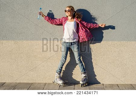 Young girl with a bottle of water, shod in rollers. Background gray wall, copy space