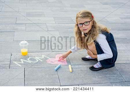 Happy Mother's Day. A little girl draws for her mother a picture surprise of crayons on the asphalt. LOVE MOM