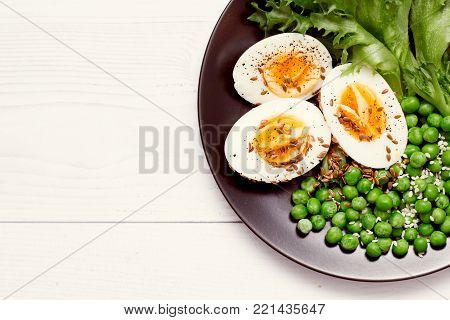 Organic ingredients for a salad with lettuce, frozen peas and eggs on rustic background. Healthy food, or diet nutrition concept. Top view.