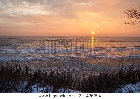 Scenic Winter Sunrise Landscape. Scenic sunrise reflection over the icy Great Lakes horizon on the coast of Lake Huron from an overlook in Port Sanilac, Michigan.