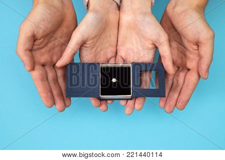 Women's hand goes to the man's hand on blue background. A man is holding wedding rings on a satin box in his hand. The guy makes a proposal to marry a girl and shows the ring.