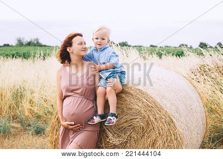 Pregnant Woman And Son On Nature. Mother Waiting Of A Second Baby.