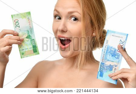 Young woman holding up cash money two thousand and hundred russian rubles notes in hand winner surprised isolated on a white background