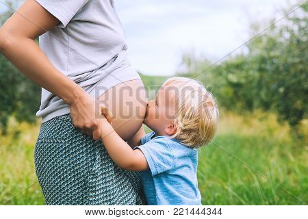 Child boy hugging and kissing belly of pregnant her mother against green nature background. Pregnant woman and her toddler son outdoors. Pregnancy, family, parenthood concepts.