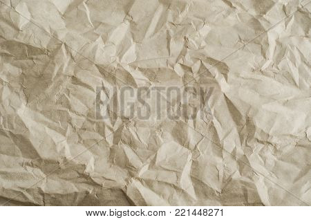 Crumpled, creased and unfolded paper background texture in a neutral parchment hue.