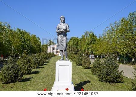 Octyabrsky, Russia - April 24, 2017: Statue of a collective farmer on a pedestal. The legacy of the Soviet era. A flower bed with tulips and young trees in the village of Oktyabrsky. Krasnodar Krai, Krasnoarmeisky District