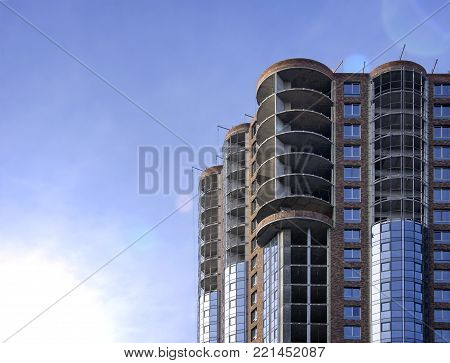 unfinished high-rise building against the blue sky, dawn