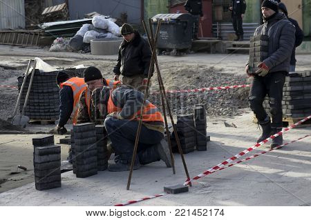 Kiev, Ukraine 10.01.2018 Repair work, workers put a pedestrian path out of tiles