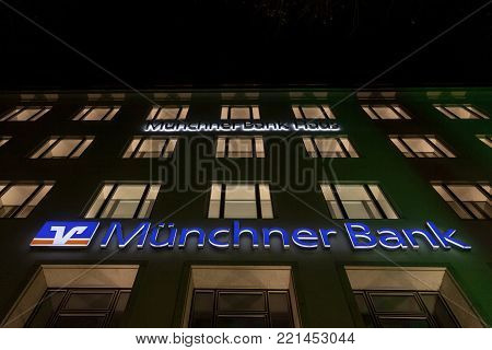 MUNICH, GERMANY - DECEMBER 17, 2017: Munchner Bank logo on their Munich main office (Munchner Bank Haus) taken at night. Munchner Bank (Bank of Munich) is the eldest and biggest credit union in Bavaria.