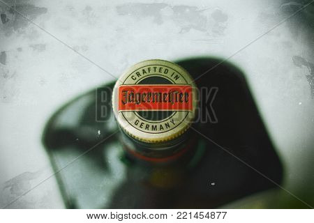 Yoshkar-Ola, Russia - December 19, 2017 Jagermeister, German digestif made with 56 herbs and spices is the flagship product of Mast-Jagermeister SE. Photo view from above, focus on the cork, shallow depth of field.