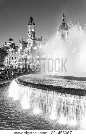 Fountain on Modernism Plaza of the City Hall of Valencia, Town hall Square, Spain. Modernisme Plaza of the City Hall of Valencia Placa del Ajuntament. Black and white vertical image. poster