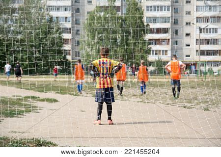 Yoshkar-Ola, Russia - August 20, 2016 Teenagers play street football in one of Yoshkar-Ola's yards. View from behind the gate.