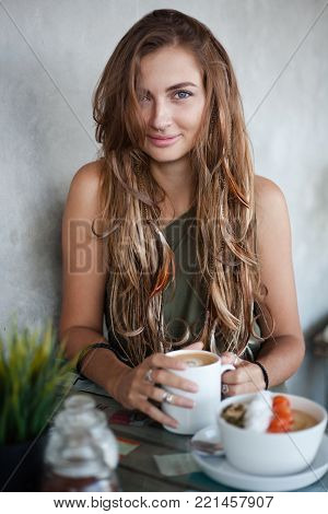 Beautiful girl with long hair with pigtails and bird feathers is sitting in a cafe. She is looking at the camera and holds a mug of coffee. A muesli bowl is on the table in front of her.