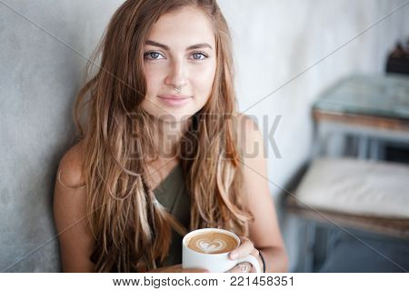 Horizontal portrait of beautiful girl is holding a mug of coffee with heart form foam. She is looking at the camera. Her long hair is with pigtails and feathers. There are gray wall on background