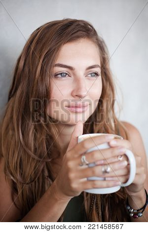 Portrait of beautiful dreaming girl with a mug of some beverage. She is looking away thoughtfully. Her long brown hair is with pigtails and feathers. There are nice silver rings on her fingers