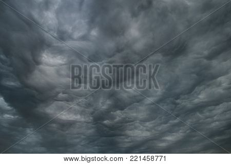 Abstract gray background of thunderous gloomy cumulus clouds, stormy sky.