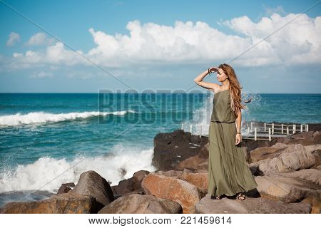 Full-length photo of a girl in a long dress standing on a stone close to ocean. Blue waves and sky with white clouds are in the background. She holds her hand by the eyes and looks into the distance