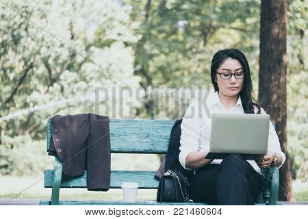 Asian business woman working on laptop while sitting on the bench in the park.