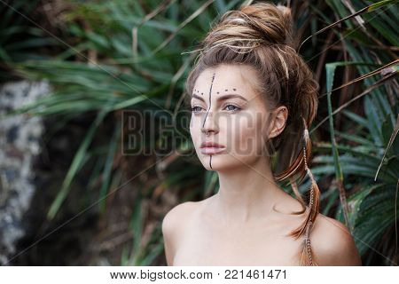 Portrait of young pretty woman with naked shoulders, painting on her face and high bunch of hair. There are black line and dots on her face. There are pigtails and feathers in hair. She looking away.